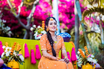 The bride looking stunning in this subtle orange outfit at her mehendi ceremony!