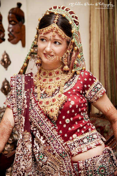 Bride covered in layers of heavy traditional bridal jewellery