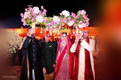 the bride enetering under a phoolon ki chadaar