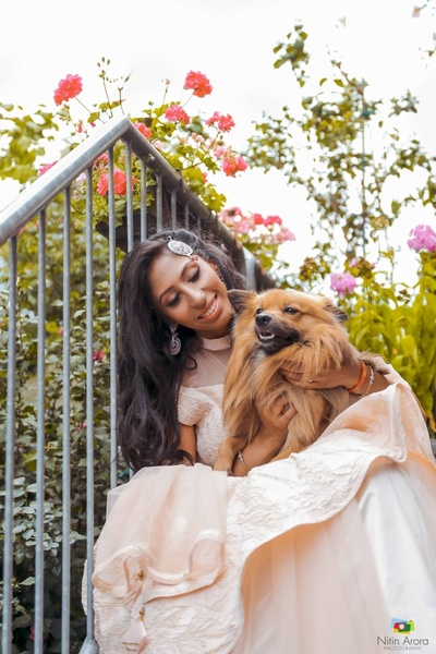 Bride Ritam poses with her pet dog during her engagement ceremony