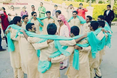 Groomsmen wearing off white kurta and pajama paired with sky blue dupattas.