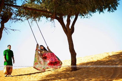 Pink flower printed lehenga styled with gold sequined choli for their pre wedding destination photo shoot in the dessert