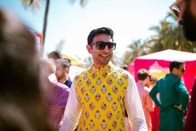 Traditional groom in a yellow bandhgala jacket for the mehndi function at The Lalit Golf and Spa Resort, Goa