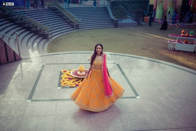 The bride is having some fun, twirling in her pretty orange and pink lehenga!