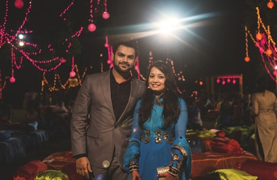 Gun metal suit styled with a black shirt. Bride wearing blue Anarkali lehenga cinched at the waistline and embellished with zari work