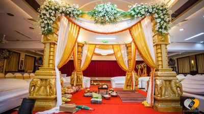 Vedi mandap setup with white and gold drapes edged in marigold sculpted gold pillars, festooned marigold strings and white floral arrangement