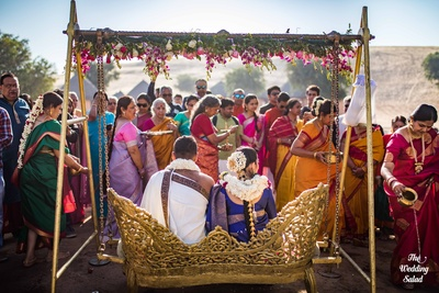 The bride and groom sitting on a swing, surrounded by family members, as part of a Tamil ritual.