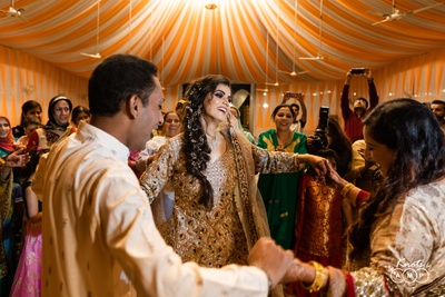 A candid moment caught of the glowing bride sharing a dance with her friends and family.