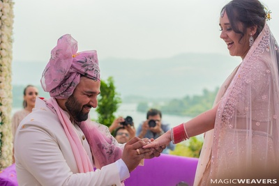 The groom slipping the ring on the bride's finger