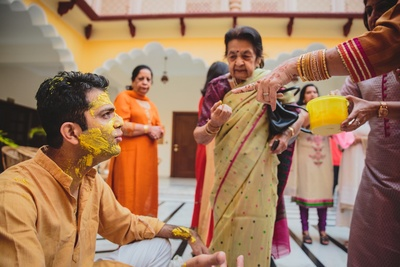 Grooms face filled with haldi for the haldi ceremony.