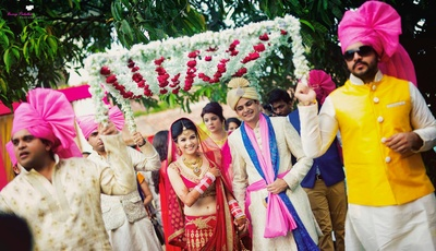 Bride decked in red embellished wedding lehenga and groom donning an ivory textured sherwani for the wedding