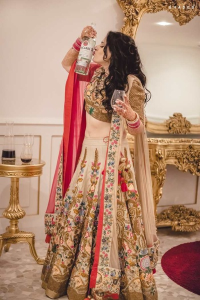 Bride Kanika in a quirky pose with alcohol during her reception party!