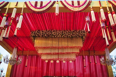 Mandap decorated with red drapes and white flowers.