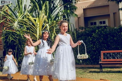Flower girls dressed up in white dresses and walking down the aisle.