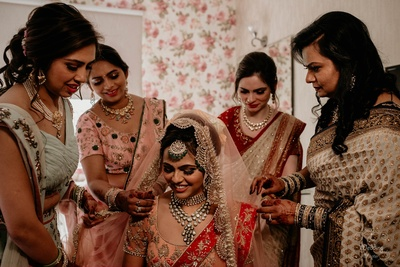 Bride's sisters helping her get ready for the most special day of her life.