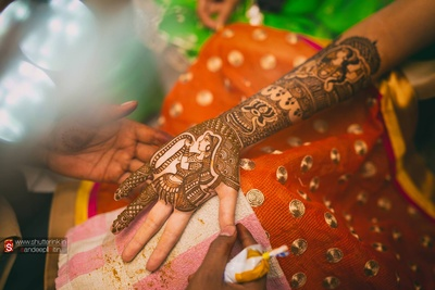 Bridal arms covered with intricately patterned mehendi designs featuring bridal portraits