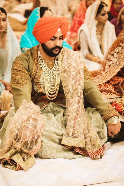 Thr groom is slooking absolutely stately in this olive green and oufit oaired with an orange turban and some stunning jewels