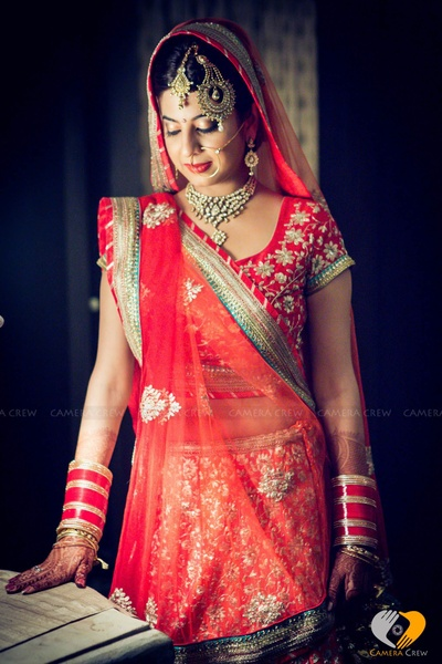Blood red wedding lehenga with heavy and detailed threadwork and gottapatti work details
