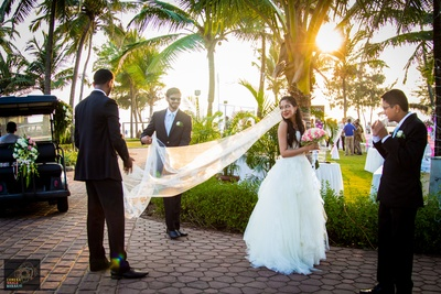 White off-shoulder tie-back wedding gown styled with sheer bridal veil and loose curls