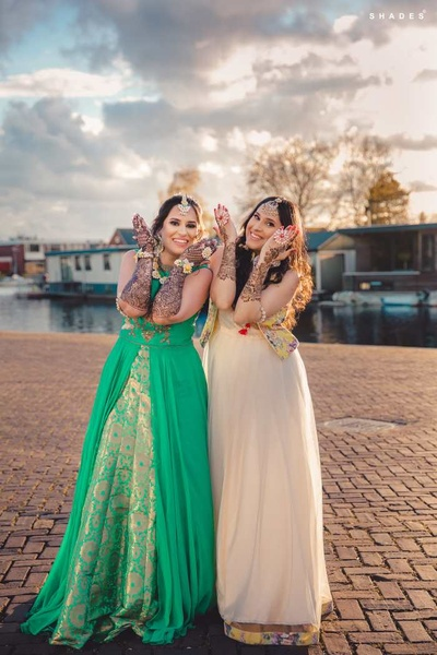 Bride and bridesmaids showing off her mehndi design