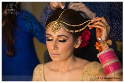Gold eye shadow, bold eye liner and blush on giving her a radiant makeup look by MUA- Guru Singh