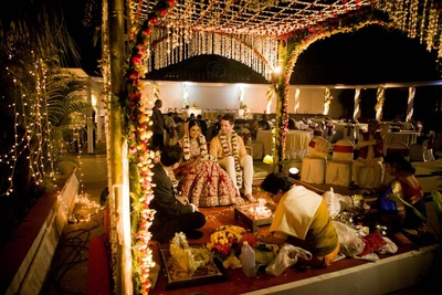 Open Air vedi mandap decorated with floral arbor, series lights, strings using Tube Roses. red Roses and Mogra
